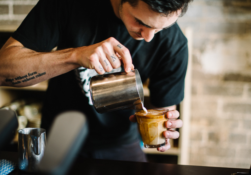 A barista pours a coffee into a glass